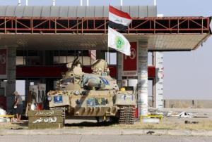 File photo of a tank belonging to the Shi'ite Badr Brigade militia taking position in front of a gas station in Suleiman Beg, northern Iraq