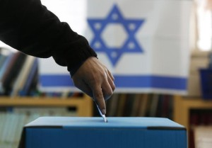 An Israeli flag is seen in the background as a man casts his ballot at a polling in a West Bank Jewish settlement, north of Ramallah