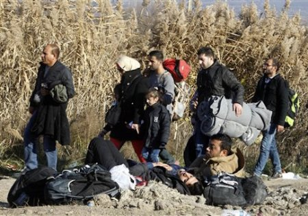 Migrants and refugees walk towards the border with Serbia, while other migrants, who were not allowed to cross into Serbia, lie on the ground awaiting for a solution, near the village of Tabanovce, in northern Macedonia, Thursday, Nov. 19, 2015. Four nations along Europe's Balkan refugee corridor shut their borders Thursday to those not coming from war-torn countries such as Syria, Afghanistan or Iraq, leaving thousands of others seeking a better life in Europe stranded at border crossings. (AP Photo/Boris Grdanoski)