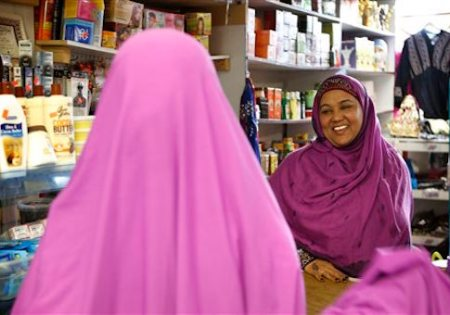 """In this Tuesday, Jan. 26, 2016 photo, Shukri Abasheikh, owner of Mogadishu Store, speaks with a customer in Lewiston, Maine. """"When Somalis came in, Lewiston people, Maine people, they think they need welfare but we don't need welfare. We need jobs. We need peace. We need education,"""" said Abasheikh, who worked as a janitor before achieving her dream of running her own business. (AP Photo/Robert F. Bukaty)"""