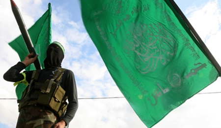 epa01962019 A Palestinian Hamas masked militant stands near a Hamas flag as he takes part in protest and a military parade in central Gaza Strip, 11 December 2009. Israeli settlers vandalized a mosque in a northern West Bank village early 11 December, spray-painting hate slogans in Hebrew and setting ablaze bookshelves and a carpet, Palestinian police and the Israeli military said. Palestinian police spokesman Munir Jagoub told the German Press Agency dpa that the fire in the grand mosque in the village of Yasouf, south-west of the city of Nablus, in the northern West Bank, caused heavy damage to the library, where copies of the Holy Quran are kept, as well as to prayer rugs and the wall. EPA/MOHAMMED SABER I