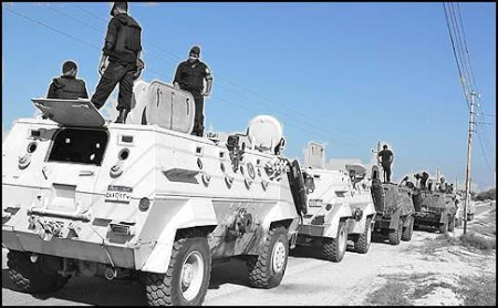 """Egyptian security forces stand by their Armoured Personell Carriers ahead of a military operation in the northern Sinai peninsula on August 08, 2012. Egypt, which launched air raids against Islamist militants in Sinai for the first time in decades, faces a tough enemy that has used the peninsula's rugged terrain to evade capture in the past. The military said it deployed Apache helicopter gunships in the strikes that killed 20 """"terrorists"""" in the Sinai village of Tumah, in retaliation for a weekend ambush that cost the lives of 16 soldiers. AFP PHOTO/STRINGERSTRINGER/AFP/GettyImages"""