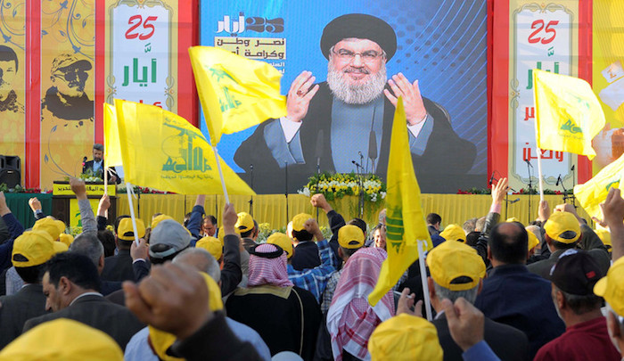 People watch Lebanon's Hezbollah leader Sayyed Hassan Nasrallah as he appears on a screen during a live broadcast to speak to his supporters at an event marking Resistance and Liberation Day, in Bekaa valley May 25, 2016. The event is to commemorate the 16th anniversary of Israel's withdrawal from southern Lebanon. REUTERS/Hassan Abdallah - RTSFWSN