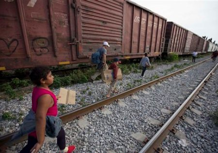 FILE - In this July 12, 2014 file photo, migrants walk along the rail tracks after getting off a train during their journey toward the U.S.-Mexico border in Ixtepec, Mexico. Many of the immigrants recently flooding the nationís southern border say theyíre fleeing violent gangs in Central America. These gangs were a byproduct of U.S. immigration and Cold War policies, specifically growing from the increase in deportations in the 1990s. With weak dysfunctional governments at home, U.S. street gang culture easily took hold and flourished in these countries. (AP Photo/Eduardo Verdugo)