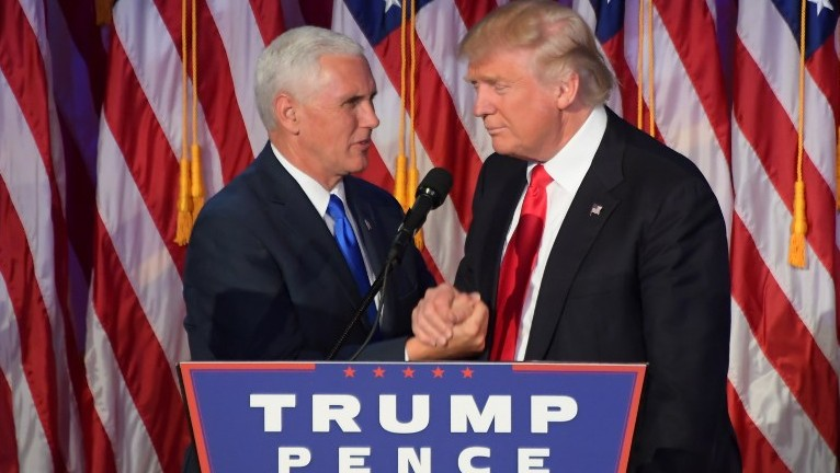 Republican president-elect Donald Trump (R) shakes hands with his running mate Mike Pence at the New York Hilton Midtown in New York on November 9, 2016. (AFP PHOTO/JIM WATSON)