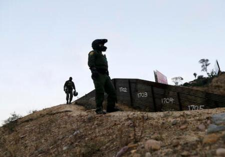 FILE - In this Wednesday, June 22, 2016, file photo, Border Patrol agents look over the primary fence separating Tijuana, Mexico, right, and San Diego in San Diego. An estimated 40 percent of the 11.4 million people in the U.S. illegally overstayed visas, a crucial but often overlooked fact in the immigration debate. More people overstayed visas than were caught crossing the border illegally. (AP Photo/Gregory Bull, File)