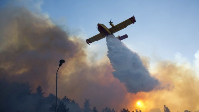 A firefighting plane from Greece fights a wildfire over Haifa, Israel, Thursday, Nov. 24, 2016. (AP Photo/Ariel Schalit)