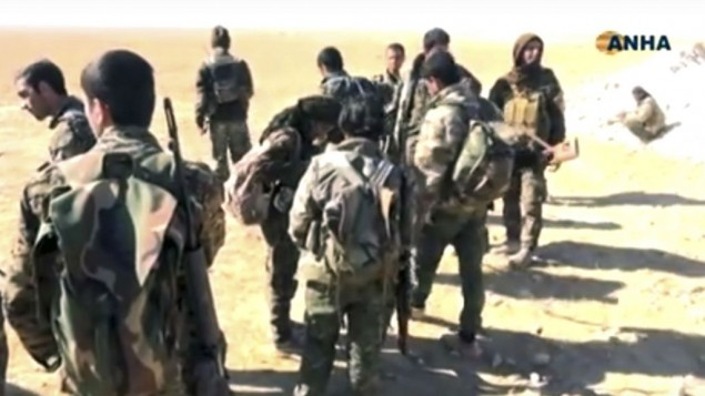 This frame grab from video provided on Monday, Nov. 7, 2016, by the Hawar News Agency, shows US-backed fighters deployed during fighting with the Islamic State group in the village of Laqtah, north of Raqqa, Syria. (Hawar News Agency, via AP)