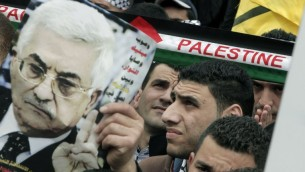 A man holds up an image of Palestinian Authority President Mahmoud Abbas as Palestinians rally in the center of the West Bank city of Nablus in support of Abbas during his visit to Washington, March 17, 2014. (Jaafar/ Ashtiyeh/AFP)