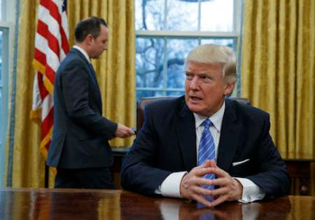 President Donald Trump sits at his desk as he waits for White House Chief of Staff Reince Priebus, left, to deliver three executive orders for his signature, Monday, Jan. 23, 2017, in the Oval Office of the White House in Washington. (AP Photo/Evan Vucci)
