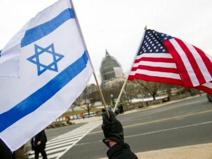 "A pro-Israel demonstrators waves flags, toward the Capitol in Washington, Tuesday, March 3, 2015, as Israeli Prime Minister Benjamin Netanyahu addressed a joint meeting of Congress. In a speech that stirred political intrigue in two countries, Netanyahu told Congress that negotiations underway between Iran and the U.S. would ""all but guarantee"" that Tehran will get nuclear weapons, a step that the world must avoid at all costs. (AP Photo/Cliff Owen)"