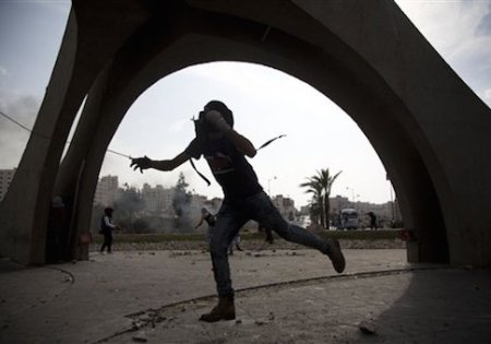 A Palestinian hurls a stone during clashes with Israeli troops, near Ramallah, West Bank, Tuesday, Oct. 20, 2015. U.N. Secretary-General Ban Ki-moon called for calm during a surprise visit to Jerusalem on Tuesday ahead of meetings with Israeli and Palestinian leaders, in a high-profile gambit to bring an end to a monthlong wave of violence. (AP Photo/Majdi Mohammed)