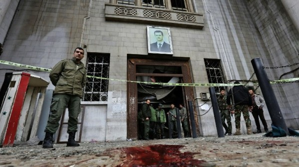 Syrian security forces gather under a portrait of Syrian President Bashar Assad at the old palace of justice building in Damascus following a reported suicide bombing on March 15, 2017. (AFP Photo/Louai Beshara)
