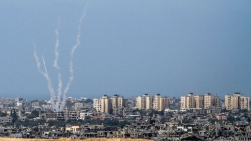Illustrative: A photo taken from the Israeli side of the Israel-Gaza border shows rockets being fired by Palestinian terrorists from the Gaza Strip into Israel, August 20, 2014. (Albert Sadikov/Flash90)