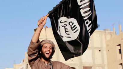 Illustrative: An Islamic State terrorist waves the jihadist organization's flag (CC BY-SA Alatele fr, Flickr)