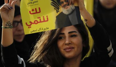 """A supporter of Hezbollah leader Sayyed Hassan Nasrallah holds up his portrait with Arabic words that read: """"We belong with you,"""" during an election campaign speech in a southern suburb of Beirut, Lebanon, Friday, April 13, 2018. Nasrallah says Monday's attack on the T4 air base ushers in a new phase that puts Israel in a state of """"direct confrontation"""" with the Islamic Republic of Iran. (AP Photo/Hussein Malla)"""