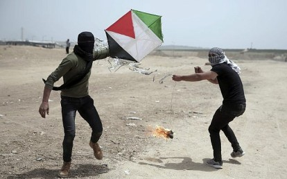 Illustrative: Palestinian protesters fly a kite with a burning rag dangling from its tail, during a protest at the Gaza Strip's border with Israel, April 20, 2018. Activists use kites with firebombs and burning rags dangling from their tails to set ablaze drying wheat fields on the Israeli side. (AP Photo/Khalil Hamra)