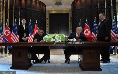 US President Donald Trump (2nd R) and North Korea's leader Kim Jong Un (2nd L) sign documents as US Secretary of State Mike Pompeo (R) and the North Korean leader's sister Kim Yo Jong (L) look on at a signing ceremony during their historic US-North Korea summit, at the Capella Hotel on Sentosa island in Singapore on June 12, 2018. (SAUL LOEB / AFP)