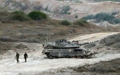 Israeli soldiers walk near an army tank patrolling along the border between Israel and the Gaza Strip on May 29, 2018. (AFP/Jack Guez)