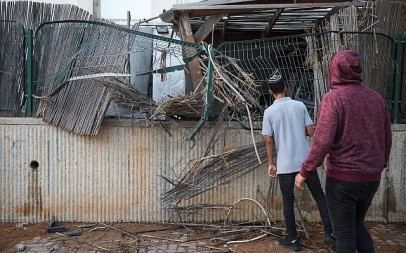 People at the scene where a courtyard of a house was hit by a Gaza rocket in the southern Israeli city of Sderot, on July 14, 2018. (Hadas Parush/Flash90)