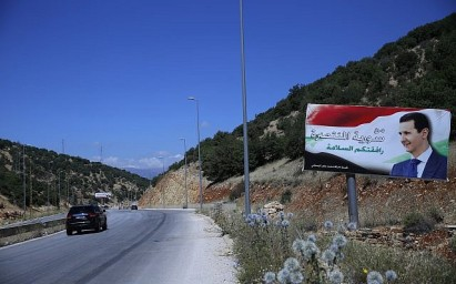 "In this July 20, 2018, photo, a poster of President Bashar Assad with Arabic that reads ""Welcome in victorious Syria."" is seen on the border between Lebanon and Syria. (AP Photo/Hassan Ammar)"