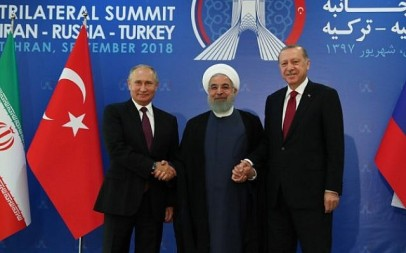 A handout picture taken and released on September 7, 2018 by the Turkish Presidential Press service shows Turkish President Recep Tayyip Erdogan (R) , Iranian President Hassan Rouhani (C) and Russian President Vladimir Putin (L) joining hands  during a trilateral summit in Tehran. (AFP/Turkish Presidency Press Office)