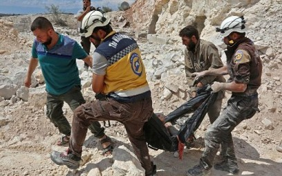 Members of the Syrian Civil Defense, also known as the 'White Helmets,' carrying a victim after airstrikes in Kafr Ain in the Idlib province, September 7, 2018. (AFP/Anas al-Dyab)