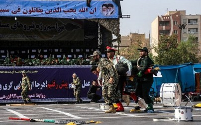 This picture taken on September 22, 2018 in the southwestern Iranian city of Ahvaz shows Iranian soldiers carrying away an injured colleague at the scene of an attack on a military parade that was marking the anniversary of the outbreak of its devastating 1980-1988 war with Saddam Hussein's Iraq. (AFP/ ISNA / MORTEZA JABERIAN)