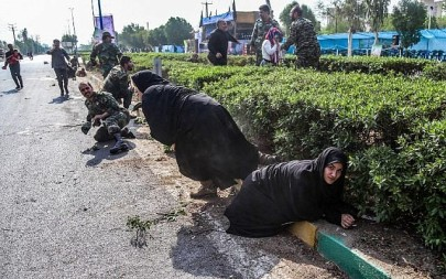This picture taken on September 22, 2018 in the southwestern Iranian city of Ahvaz shows Iranian women and soldiers taking cover next to bushes at the scene of an attack on a military parade in the southwestern Khuzestan province on September 22, 2018. (AFP/ ISNA / MORTEZA JABERIAN)