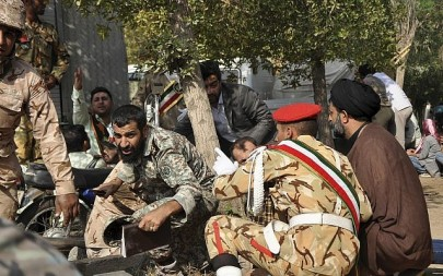 In this photo provided by the Iranian Students' News Agency, ISNA, Iranian armed forces members and civilians take shelter in a shooting during a military parade marking the 38th anniversary of Iraq's 1980 invasion of Iran, in the southwestern city of Ahvaz, Iran, Sept. 22, 2018 (AP Photo/ISNA, Behrad Ghasemi)