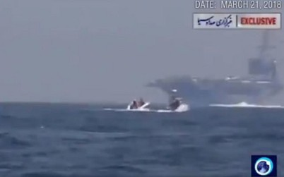 A still from a video published by Iranian state media showing a boat approaching a US carrier in March, 2018. (screen capture: Twitter)