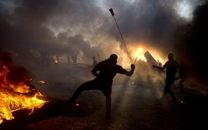 Black smoke from burning tires covers the sky as Palestinian protesters hurl stones toward Israeli troops during a protest at the Gaza Strip's border with Israel, Oct. 12, 2018. (AP Photo/Khalil Hamra)