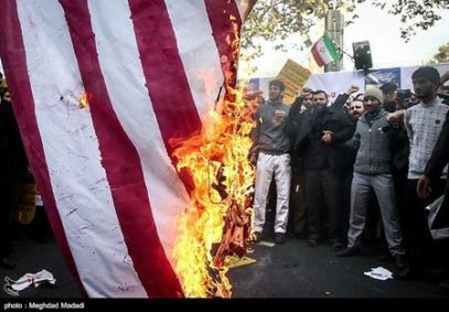 Iranian people burn the U.S. flag as they mark the anniversary of the seizure of the U.S. Embassy, in Tehran