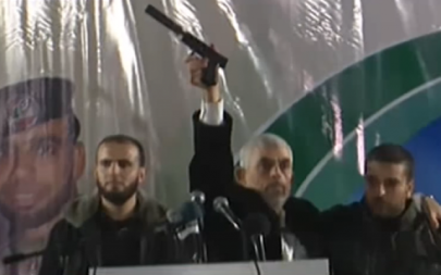 In this November 16, 2018 image, Hamas's Gaza chief Yahya Sinwar holds up a handgun with a silencer he says was captured from Israeli special forces during a firefight in the Gaza Strip on November 11 (YouTube screenshot)