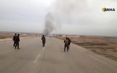 Screen capture from video provided by Hawar News, ANHA, shows Kurdish fighters standing guard at the site of a suicide attack near the town of Shaddadeh, in Syria's northeastern province of Hassakeh, Syria, January 21, 2019. (ANHA via AP)
