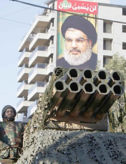 A Shia Hezbollah supporter stands on a rocket launcher in Nabatieh with a poster of Hezbollah leader Sayyed Hassan Nasrallah in the background. (Reuters)