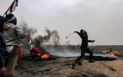 A Palestinian protester uses a slingshot to hurl a rock toward Israeli forces during clashes following a demonstration along the border with Israel in Malaka east of Gaza City on March 30, 2019 (Mahmud Hams/AFP)