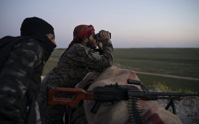 In this Tuesday, Feb. 19, 2019 file photo, US-backed Syrian Democratic Forces fighters watch as an airstrike hits territory still held by Islamic State in the desert outside Baghouz, Syria (AP Photo/Felipe Dana, File)