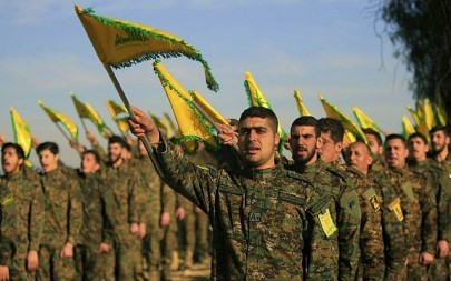 Hezbollah fighters hold flags, as they attend the memorial of their slain leader Sheik Abbas al-Mousawi, who was killed by an Israeli airstrike in 1992, in Tefahta village, south Lebanon, February 13, 2016. (Mohammed Zaatari/AP)