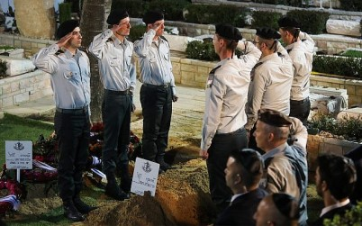 Israeli soldiers salute near the fresh grave of Zachary Baumel, during his funeral at the Mount Herzl Military cemetery in Jerusalem, April 4, 2019. (Hadas Parush/Flash90)