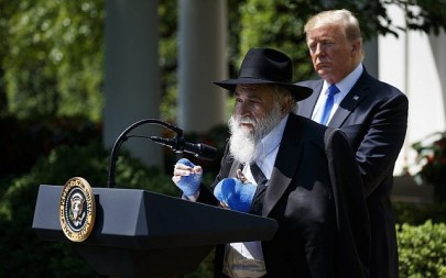 President Donald Trump looks on as Rabbi Yisroel Goldstein, survivor of the Poway, Calif synagogue shooting, speaks during a National Day of Prayer event in the Rose Garden of the White House, May 2, 2019. (AP/Evan Vucci)