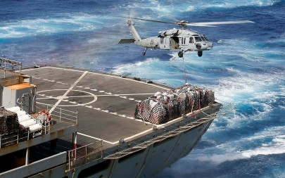 A helicopter loads cargo onto the deck of the USS Abraham Lincoln aircraft carrier in the Mediterranean Sea as the ship's strike group makes its way to the Persian Gulf, May 8, 2019. (US Navy/Michael Singley)