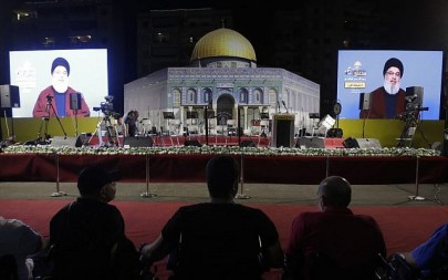 Lebanese Shiite Muslims listen to a speech by the head of the terror group Hezbollah, Hassan Nasrallah, transmitted on two large screens with a replica of the Dome of the Rock mosque, during the al-Quds (Jerusalem) International Day, in a southern suburb of the capital Beirut on May 31, 2019 (Anwar AMRO / AFP)
