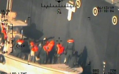 This image released by the US Department of Defense on Monday, June 17, 2019, and taken from a US Navy helicopter, shows what the Navy says are members of the Islamic Revolutionary Guard Corps Navy removing an unexploded limpet mine from the M/T Kokuka Courageous. (US Department of Defense via AP)