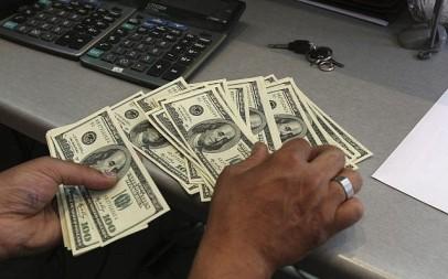 A currency exchange bureau worker, counts US dollars, in downtown Tehran, Iran, June 9, 2011. (AP/Vahid Salemi)