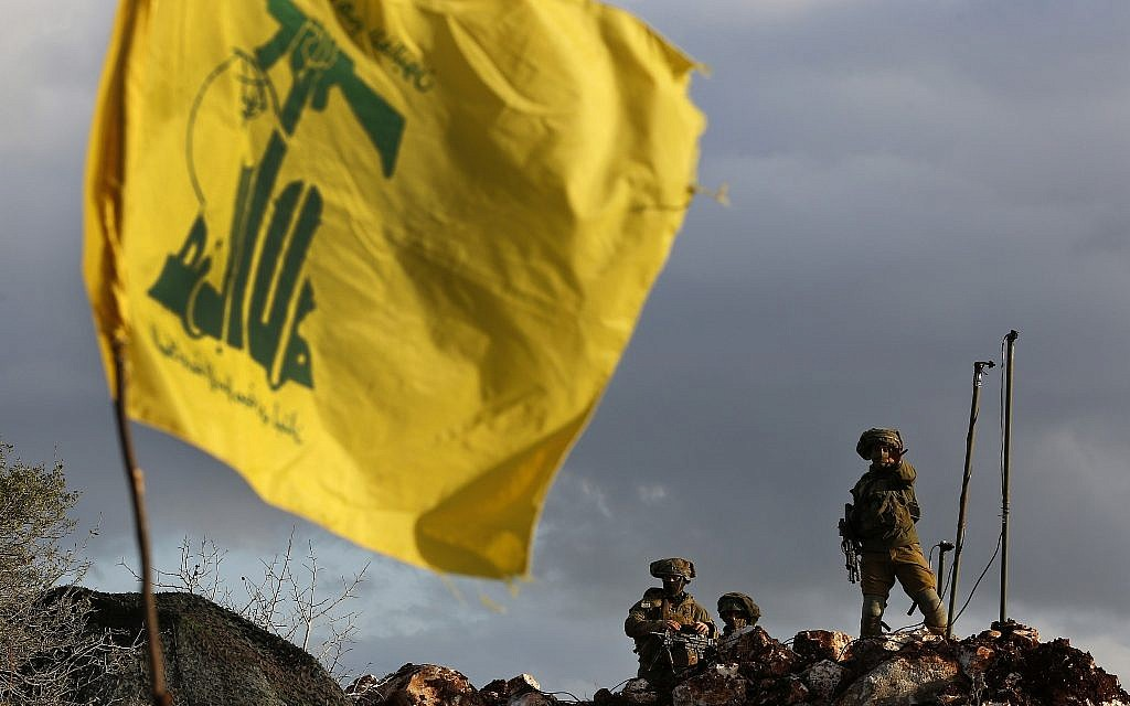 In this photo from December 13, 2018, Israeli soldiers stand guard next to cameras at their new position in front of a Hezbollah flag, near the Lebanese southern border village of Mays al-Jabal, Lebanon. (AP Photo/Hussein Malla)