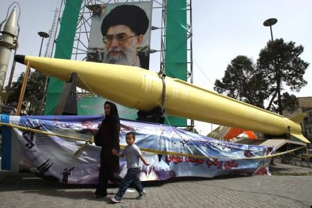 A woman and boy walk past Shahab-2 (L) and Shahab-3 missiles on display in Tehran in 2008 (file)