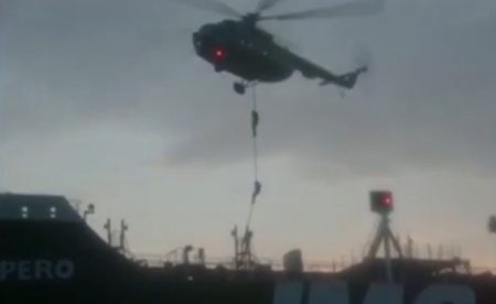 Soldiers abseil from a hovering helicopter while gunboats surrounding the Impero force it north towards Bandar Abbas
