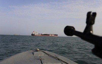 A speedboat of Iran's Revolutionary Guard trains a weapon toward the British-flagged oil tanker Stena Impero, which was seized in the Strait of Hormuz by the Guard, in the Iranian port of Bandar Abbas, July 21, 2019. (Morteza Akhoondi/Tasnim News Agency via AP)