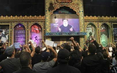 Supporters of the Lebanese Shiite terror group Hezbollah react with clenched fists as they watch a speech by the movement's leader Hasan Nasrallah, transmitted on a large screen in the Lebanese capital Beirut's southern suburbs on September 2, 2019. (Photo by AFP)